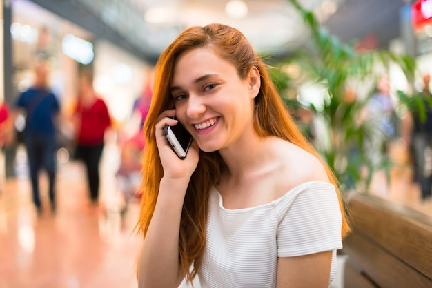 Young redhead pretty girl in a shopping center keeping a conversation with the mobile