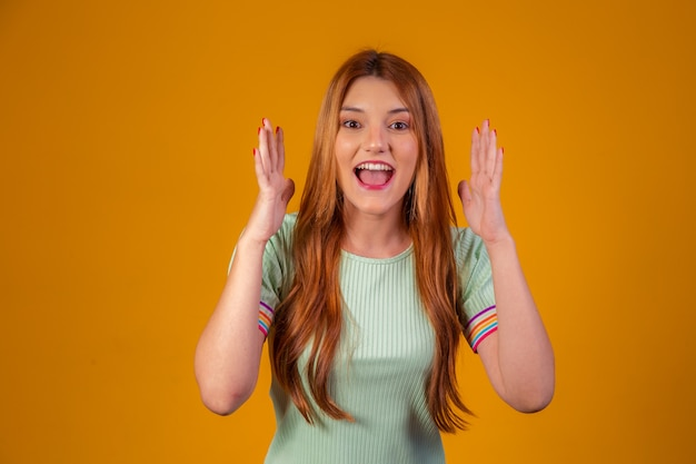 Young redhead shocked and surprised on yellow background.
