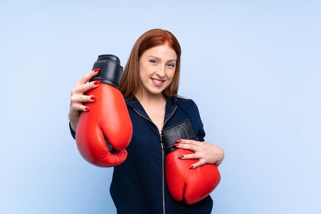 Рыжая молодая спортивная женщина на синем фоне с боксерскими перчатками