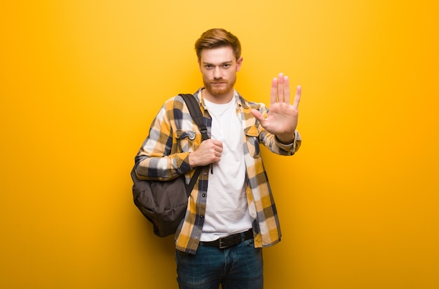 Young redhead student man putting hand in front