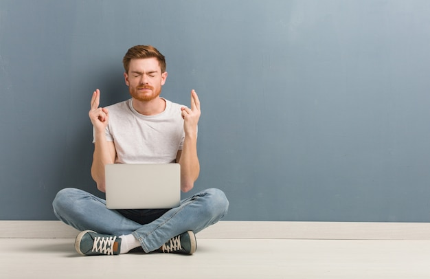 Young redhead student man sitting on the floor crossing fingers, holding a laptop.