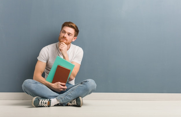 Young redhead student man sitting on the floor doubting and confused. he is holding books.