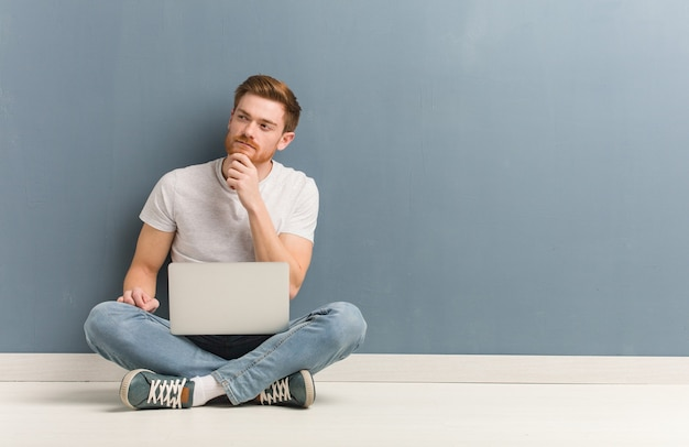 Young redhead student man sitting on the floor doubting and confused. he is holding a laptop.