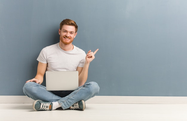 Young redhead student man sitting on the floor pointing to the side with finger. he is holding a laptop.