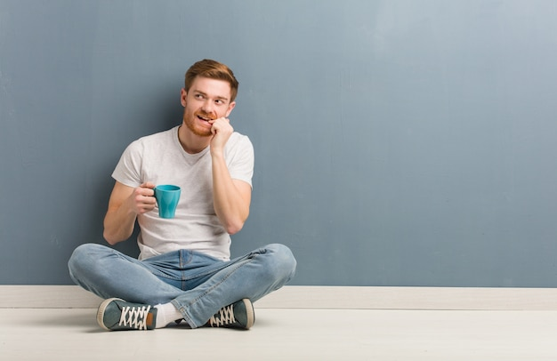 Young redhead student man sitting on the floor relaxed thinking about something looking at a copy space. he is holding a coffee mug.