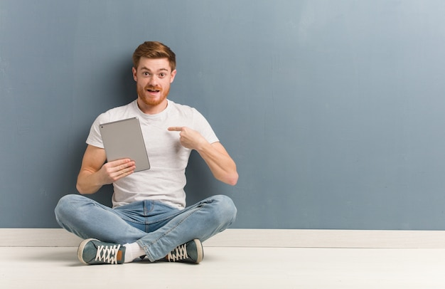 Young redhead student man sitting on the floor surprised, feels successful and prosperous. he is holding a tablet.