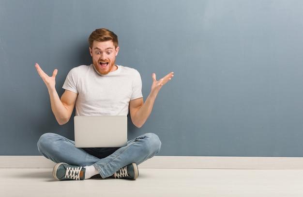 Молодой рыжий студент человек сидит на полу, празднует победу или успех. он держит ноутбук.