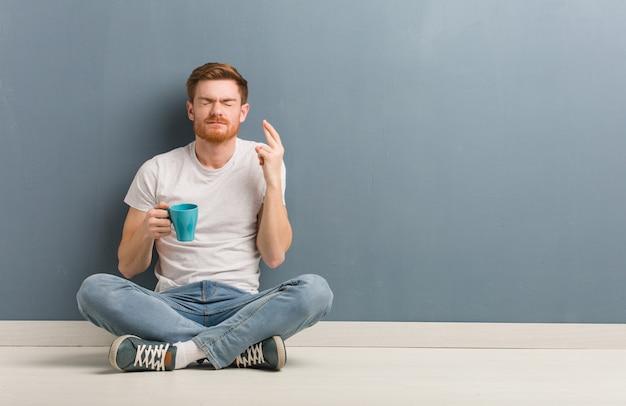 행운을 위해 손가락을 건너 바닥에 앉아 젊은 빨간 머리 학생 남자. 그는 커피 잔을 들고있다.