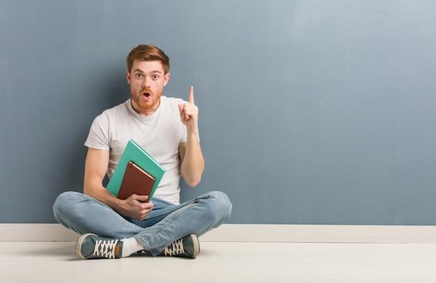 좋은 아이디어, 창의성의 개념을 갖는 바닥에 앉아 젊은 빨간 머리 학생 남자.