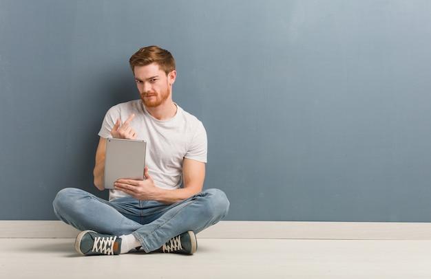 와 서 초대하는 바닥에 앉아 젊은 빨간 머리 학생 남자. 그는 태블릿을 들고있다.