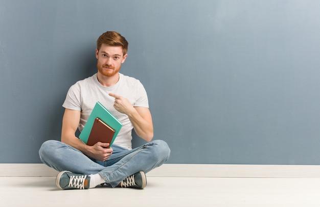 와 서 초대하는 바닥에 앉아 젊은 빨간 머리 학생 남자. 그는 책을 들고있다.