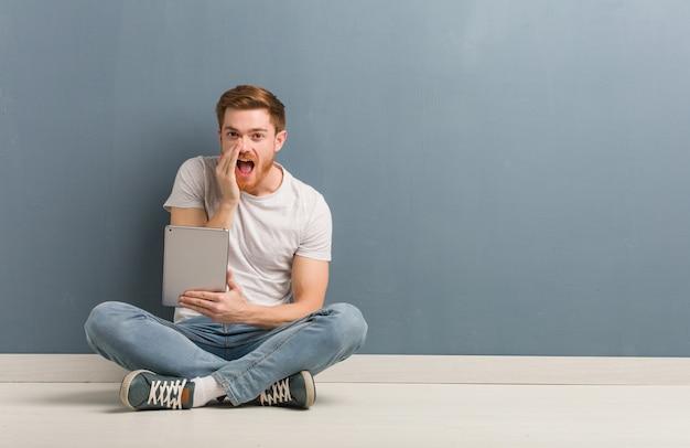 Молодой рыжий студент человек сидит на полу, крича что-то счастливое на фронт. он держит планшет.