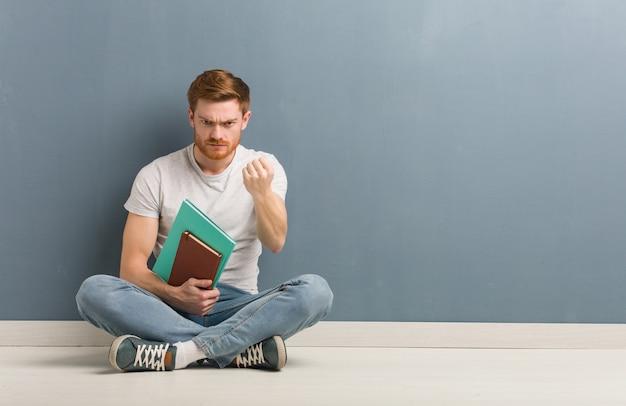 젊은 빨강 머리 학생 남자 주먹 앞에, 화가 식을 보여주는 바닥에 앉아. 그는 책을 들고있다.