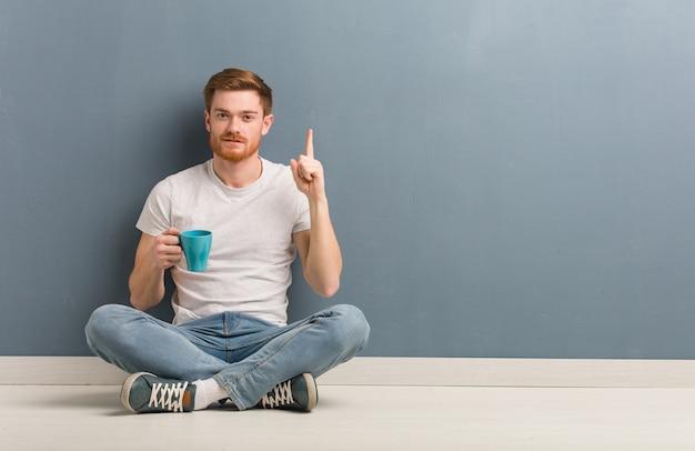 번호 하나를 보여주는 바닥에 앉아 젊은 빨강 머리 학생 남자. 그는 커피 잔을 들고있다.