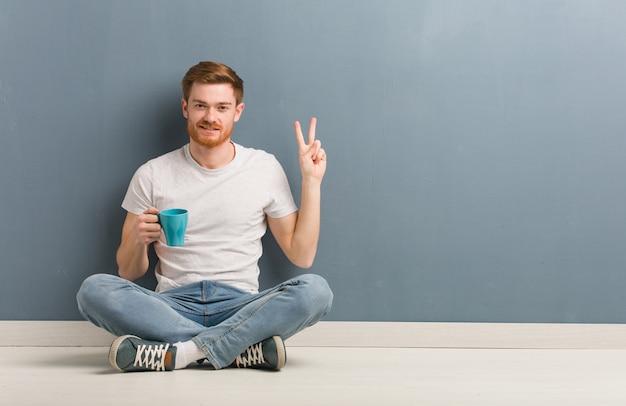 번호 2를 표시하는 바닥에 앉아 젊은 빨간 머리 학생 남자. 그는 커피 잔을 들고있다.
