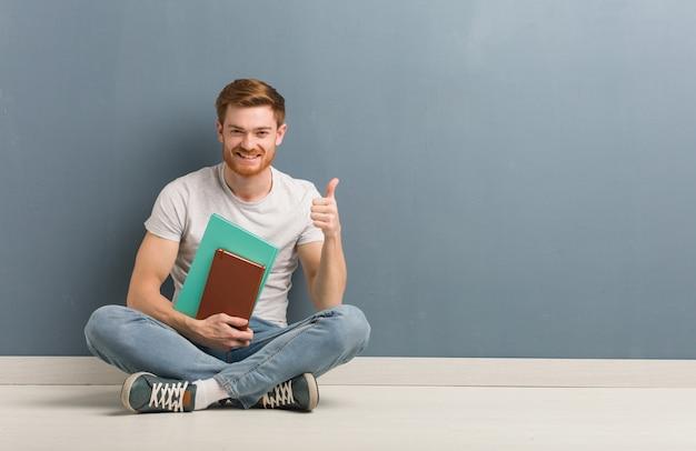 웃 고 엄지 손가락을 올리는 바닥에 앉아 젊은 빨간 머리 학생 남자. 그는 책을 들고있다.