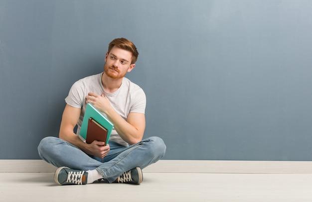 자신감과 팔을 교차, 웃 고 바닥에 앉아 젊은 빨간 머리 학생 남자.
