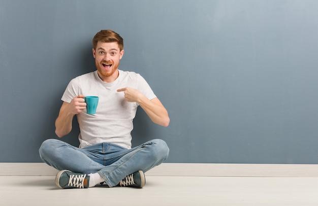 놀란 바닥에 앉아 젊은 빨간 머리 학생 남자는 성공과 번영을 느낍니다. 그는 커피 잔을 들고있다.