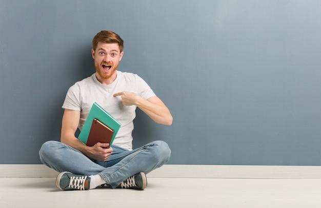 바닥에 앉아 젊은 빨강 머리 학생 남자는 성공과 번영을 느낀다. 그는 책을 들고있다.