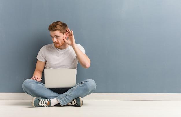 Молодой рыжий студент человек, сидящий на полу, пытается слушать сплетни. он держит ноутбук.
