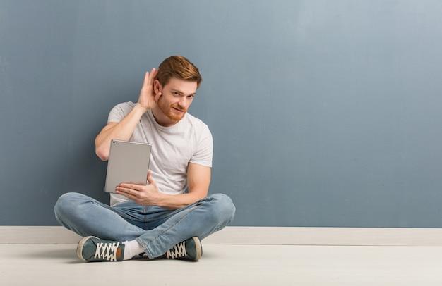 Молодой рыжий студент человек, сидящий на полу, пытается слушать сплетни. он держит планшет.