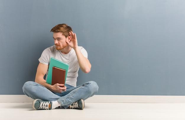 Молодой рыжий студент человек, сидящий на полу, пытается слушать сплетни он держит книги.