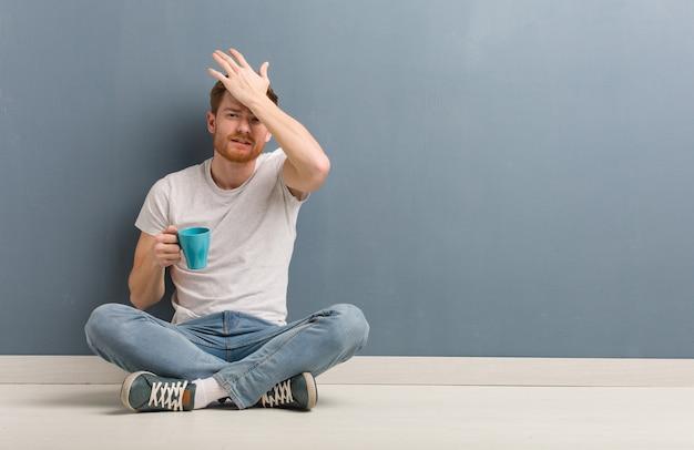 바닥에 앉아 젊은 빨간 머리 학생 남자 걱정과 압도. 그는 커피 잔을 들고있다.