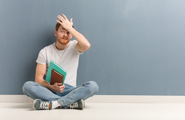 床に座っている若い赤毛の学生男は心配して圧倒されました。彼は本を持っています。