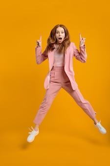 Молодая рыжая успешная бизнес-леди прыгает с поднятыми пальцами, показывая себя изолированной на желтом фоне, в розовом костюме, потрясенная, удивленная, эмоционально реагирует на что-то