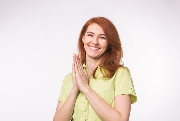 Молодая рыжая женщина хлопает в ладоши на белом фоне