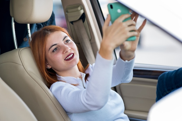 Young redhead woman driver taking selfies with her mobile phone sitting behind the wheel of the car in rush hour traffic jam.