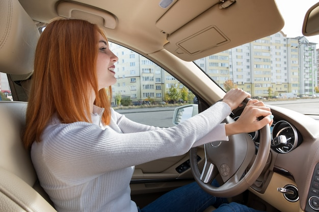 Young redhead woman driver behind a wheel driving a car smiling happily.