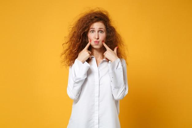 黄色いオレンジ色の壁に分離されたポーズをとってカジュアルな白いシャツを着た若い赤毛の女性の女の子