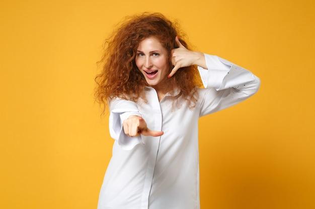 黄色いオレンジ色の壁に分離されたポーズのシャツの若い赤毛の女性の女の子