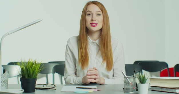 Young redhead woman in glasses has online business conference call.