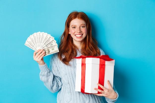 크리스마스 선물 상자와 돈을 들고 젊은 빨간 머리 여자 기쁘게 웃 고, 파란색 배경 위에 서.