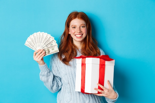 Young redhead woman holding christmas gift box and money, smiling pleased, standing over blue background.