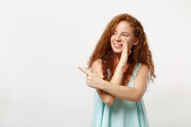 白い背景で隔離のポーズをとってカジュアルな服を着た若い赤毛の女性。人々のライフスタイルの概念。コピースペースをモックアップします。ゴシップをささやき、人差し指を脇に向けて、手のジェスチャーで秘密を伝えます。