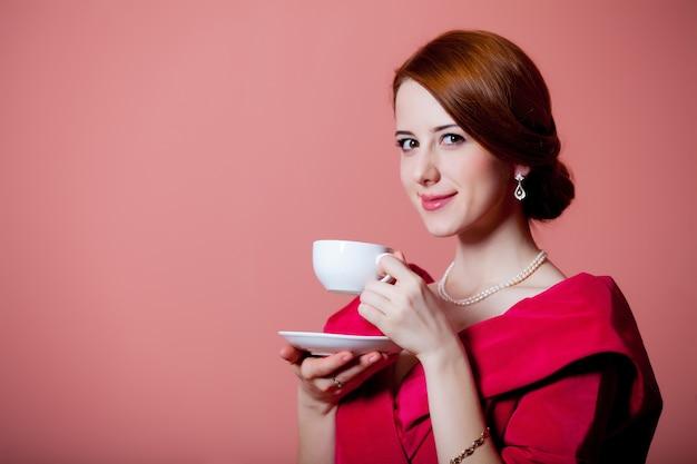 ピンクのお茶と赤のビクトリア朝時代の服の若い赤毛の女性