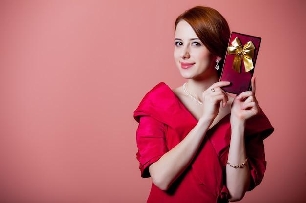 ピンクのギフトボックスと赤いビクトリア朝時代の服の若い赤毛の女性