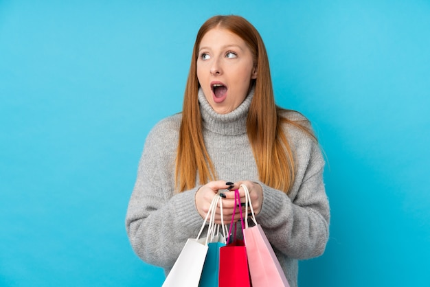 Young redhead woman over isolated blue wall holding shopping bags and surprised