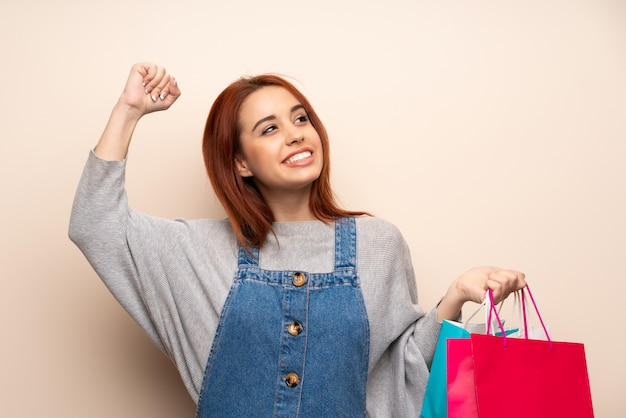 Young redhead woman over isolated holding a lot of shopping bags in victory position