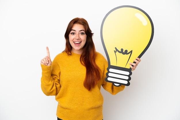 Молодая рыжая женщина, изолированные на белом фоне, держит значок лампочки и думает