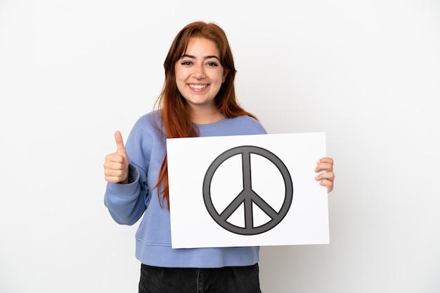 Молодая рыжая женщина, изолированная на белом фоне, держит плакат с символом мира с большим пальцем вверх