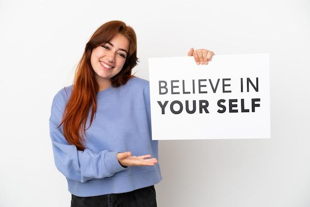 Молодая рыжая женщина, изолированные на белом фоне, держит плакат с текстом верю в себя и указывая на него
