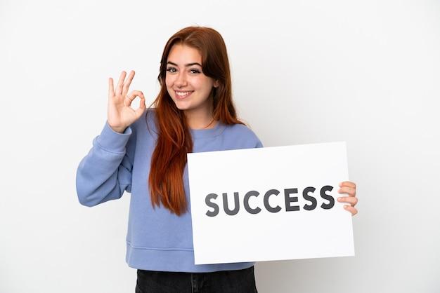 Молодая рыжая женщина, изолированные на белом фоне, держит плакат с текстом успех и празднует победу