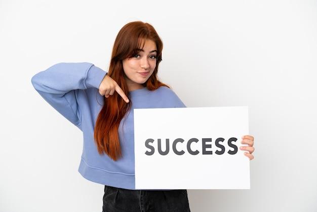 Молодая рыжая женщина изолирована на белом фоне, держа плакат с текстом успех и указывая на него