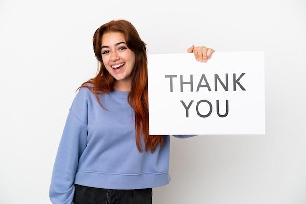 흰색 배경에 격리된 젊은 빨간 머리 여자는 행복한 표정으로 감사합니다.라는 문구가 적힌 플래카드를 들고 있습니다.