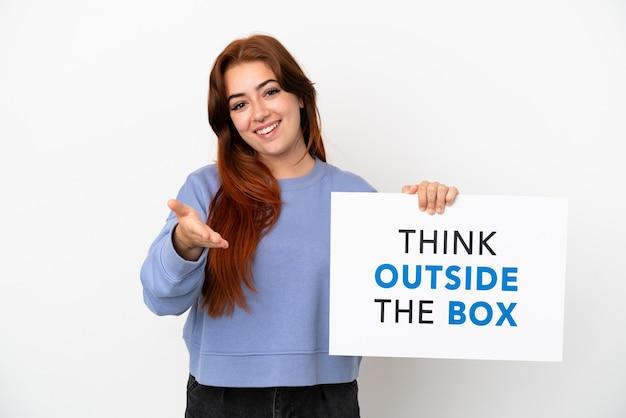 흰색 배경에 격리된 젊은 빨간 머리 여성은 'think outside the box'라는 문구가 적힌 플래카드를 들고 거래를 하고 있다