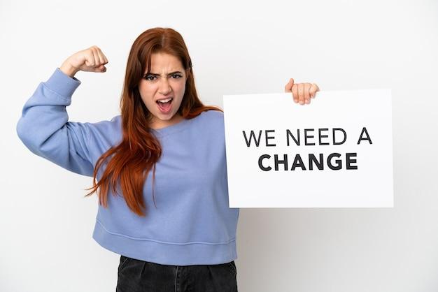 흰색 배경에 격리된 젊은 빨간 머리 여성은 우리에게 변화가 필요하다는 플래카드를 들고 강한 몸짓을 하고 있습니다.